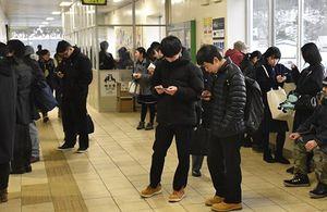 16日まで利用していた列車が17日から運休となったことを知らずに三沢駅を訪れ、学校などへの連絡に追われる生徒たち=17日午前7時43分