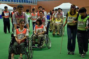 車いすの人や視覚障害のある人たちを避難誘導する参加者
