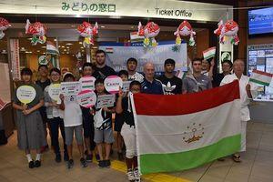 新青森駅に到着後、出迎えた市民と記念写真に納まるタジキスタンの柔道選手団=12日午後9時3分