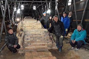完成した103メートルの登り窯を囲む、今井理桂さん(中央手前)や工事に関わったスタッフ、ボランティアら=20日正午すぎ、黒石市豊岡