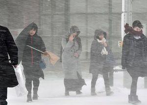 吹雪の中、厳しい寒さに肩をすぼめて歩く市民ら=27日午後3時ごろ、青森市浜田1丁目