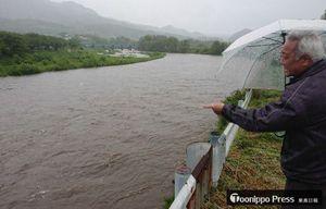 大雨で増水した馬淵川を指さし、不安がる町民=18日午後5時36分、三戸町川守田