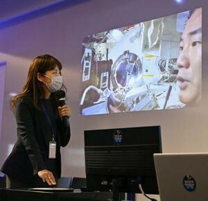 ISSの日本実験棟「きぼう」で、野口聡一さんを映し出すアバター(分身)ロボット(モニターの中央)を遠隔操作する女性=20日午後、東京都港区