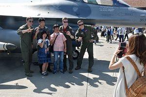 戦闘機をバックに米兵と記念撮影する来場者