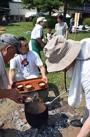 土器の鍋から縄文鍋をよそう保存協会メンバー