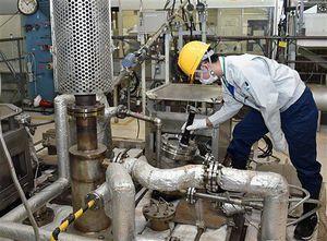 ガラスと模擬廃液を入れた炉内の状況を確認する日本原燃社員。下には高温に熱せられた溶融炉がある