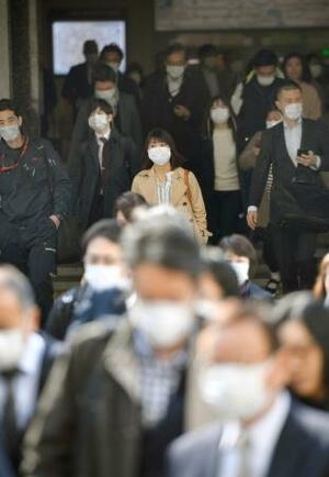 新型コロナウイルス感染者の急増を受けた東京都の小池百合子知事による要請から一夜明けた26日朝、マスク姿で出勤する人たち=東京・丸の内