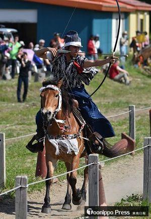 疾走する馬から的を狙う流鏑馬の射手=27日、十和田市の十和田乗馬倶楽部