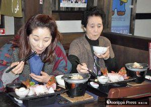 5万食目となり感謝状を受けた後、メバル膳を味わう川村さん(左)と小野さん親子