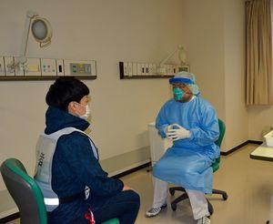 八戸市立市民病院の感染症病棟で1月に実施した新型コロナウイルス感染症患者の受け入れを想定した訓練。実際の診療も訓練と同様、医師(右)はフェースガードやマスク、ガウンなどで感染防御して行っている