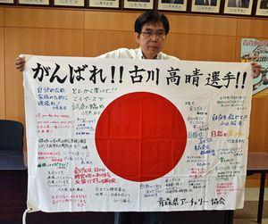 古川への応援メッセージが寄せ書きされた日の丸を持つ手塚さん