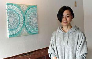 パリのアートフェアに出展する作品「サーチライト」と並んで立つサイトウさん=14日、弘前市清水のカフェ「ska vi fika?」
