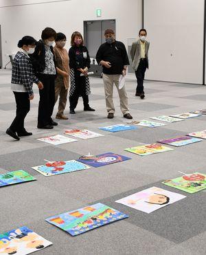 子どもたちの作品を並べ、意見を出し合う審査員たち=16日、青森市の東奥日報新町ビル