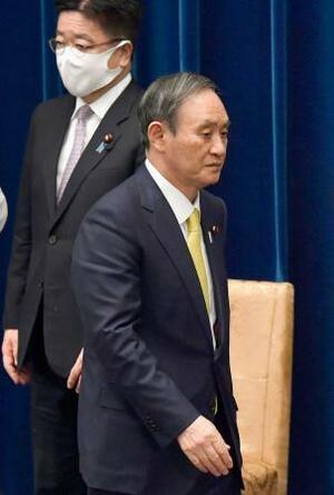 記者会見を終えて引き揚げる菅首相。奥は加藤官房長官=4日夜、首相官邸