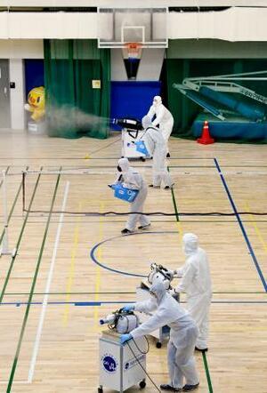 25日、ソウルの体育文化会館で行われた新型コロナウイルスの防疫処置(共同)