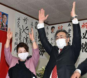 無投票で初当選を決め万歳三唱する倉光氏(右)。左は妻一恵さん=21日午後5時7分、つがる市木造朝日の事務所