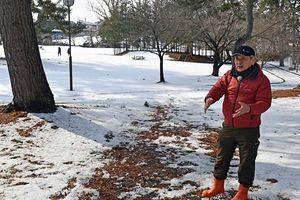 暖冬のために地面がむき出しになった五所川原市金木町の芦野公園で地吹雪体験受け入れ休止の経緯を語る角田さん=23日午前