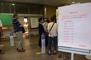 北海道新幹線の運行状況確認や切符のキャンセルなどで「みどりの窓口」に並ぶ人々。構内には運休を知らせる看板が掲げられていた=6日午前9時22分、青森市の新青森駅