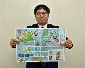 作成した八戸市中心街のマップを持つ担当者