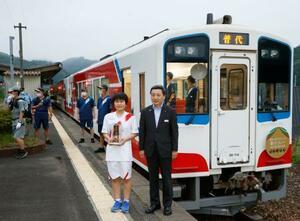 三陸鉄道の列車の前で、聖火ランナー(左)と記念撮影する中村一郎社長=16日午後、岩手県普代村の普代駅