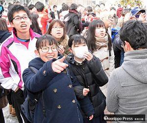 掲示板に自分の番号を見つけて喜ぶ受験生=6日午後2時ごろ、弘大文京キャンパス