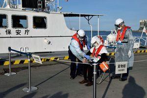 貨物船に見立てた場所で、患者役の男性(中)を搬送するために感染防止のフードを装着する検疫官(左)と医師