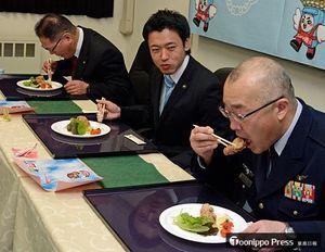 空自第42警戒群の「Sora空っ!」を試食する佐藤群司令(手前)、宮下市長(手前から2人目)ら