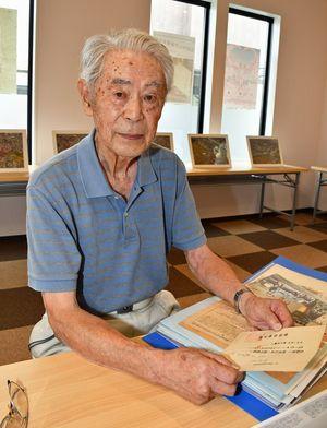 「自由に空を飛ぶほど楽しいことはない」と話す藤田さん。手にしているのは旧海軍飛行予科練習生の採用通知