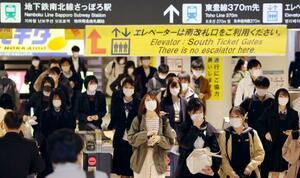 札幌市営地下鉄さっぽろ駅の改札を通るマスク姿の人たち=13日午後