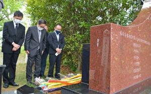 外国人捕虜の追悼碑に向かい、黙とうする被爆者の朝長万左男さん(左から2人目)ら除幕式参加者=4日、長崎市