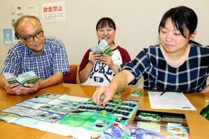 八郎湖の環境問題を学べるカードゲーム「はちリバ」で遊ぶ磯村紋加さん(中央)ら=6日、秋田市