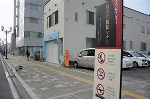 場所取りをやめることなどを呼び掛ける看板のそばにもガムテープなどで場所取りがされている=5日、弘前市駅前