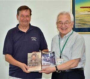 50年ぶりに三沢を訪れ、大柳館長(右)に著書を寄贈したユーリックさん