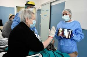 イタリア・ミラノの病院で、面会はできないため、タブレットを使って親族と話をする新型コロナウイルスの患者=7日(ロイター=共同)