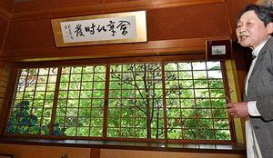 右手にコブシ、左下にアジサイを配した「涼み屋敷」の窓を飾るステンドグラスの大型作品。右端は研究家の田辺さん