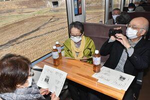 津軽鉄道の車窓から見える津軽の景色を眺めながら、千空の句を振り返る乗客ら