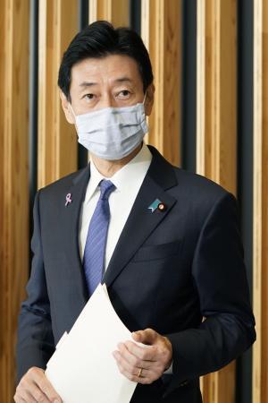 記者の質問に答える西村経済再生相=22日午前、東京・永田町