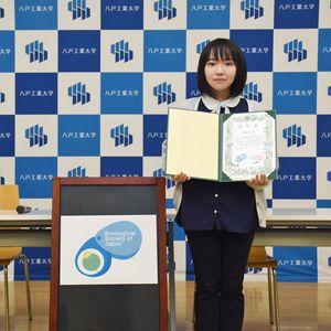 日本蘚苔類学会の新ロゴマークに採用され、同学会からの表彰状を手に作品の横に立つ貝塚さん