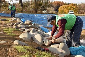 気泡緩衝材などが入った袋を環状列石の間に置いていく作業員