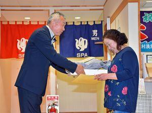 松野会長(左)から記念品を受け取る山崎さん