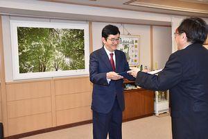 三村知事(右)から委嘱状を受けるチョ氏。後方左に飾っているのは、チョ氏が撮影した写真