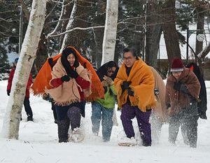 雪原に駆けだす地吹雪体験ツアーの参加者=24日午後、五所川原市金木町
