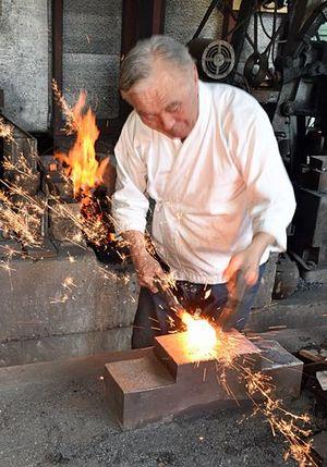 真っ赤に焼けた鋼を鍛える佐藤さん=東京・八王子市の工房