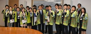 三村知事(前列中央)から任命書を受け取り、外国人客のもてなしに向けて気合を入れる県職員ら