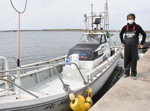 クロマグロ捕りが全面禁止となり、釣り客からのキャンセルが相次いだ遊漁船と木村さん=7日、鯵ケ沢漁港