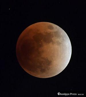 皆既月食で赤銅色に染まる月=31日午後9時58分、八戸市児童科学館屋上から