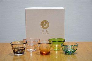 田酒の瓶やラベルの色を取り入れた津軽びいどろの杯。(前列左から)斗壜取、特別純米、山廃(後列左から)桜ラベル、四割五分