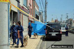捜索のため、小山さんの店舗兼自宅を出発する警察犬と指導手ら=23日午前