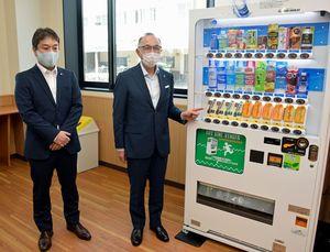 金木庁舎に設置された災害対応の自動販売機をアピールする(左から)迫上支店長、佐々木市長