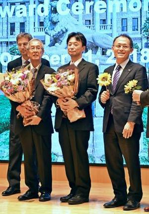 インターネット平和賞を受賞し、花束を手にする(左から)山田貴夫氏、小木曽健氏。右は選考委員を務めたICANの川崎哲国際運営委員=11日、ソウル(共同)